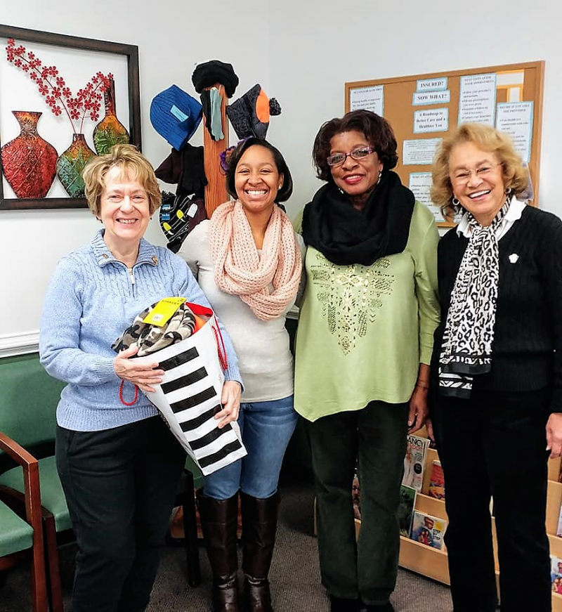 Donna and Lillian donating warm things collected by Rotarians for patrons of the Community Health Center.
